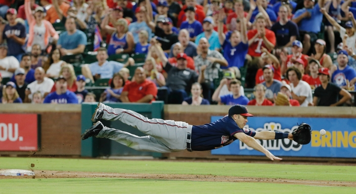 FILE - In this Saturday, July 9, 2016, file photo, Minnesota Twins first baseman Joe Mauer dives for a bad throw from second baseman Brian Dozier during the second inning of a baseball game against the Texas Rangers in Arlington, Texas. The Minneapolis Star Tribune reports that Mauer has taken out an ad in its Sunday, Nov. 11, 2018, paper to announce his retirement. (AP Photo/Brandon Wade, File)