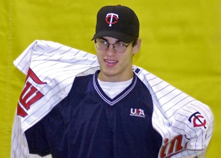 FILE - In this June 5, 2001, file photo, Joe Mauer puts on a Minnesota Twins jersey during a news conference at his high school in St. Paul, Minn., after he became the No. 1 overall pick in the Major League amateur draft. The Minneapolis Star Tribune reports that Mauer has taken out an ad in its Sunday, Nov. 11, 2018, paper to announce his retirement. (AP Photo/Jim Mone, File)