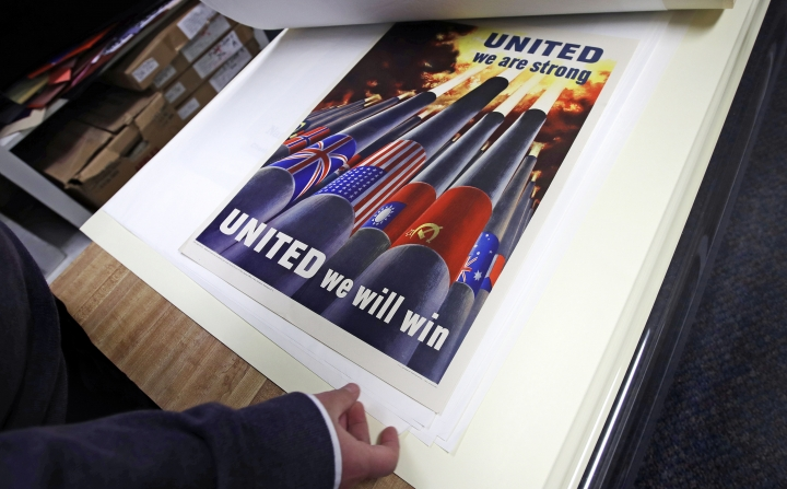 Brian Sylvester, director of the Rochester Public Library, examines original war posters at the library's archive in Rochester, N.H., Thursday, Nov. 8, 2018. A trove of propaganda posters from World War I and II were found recently found after being lost in storage for decades in the library's basement. (AP Photo/Charles Krupa)