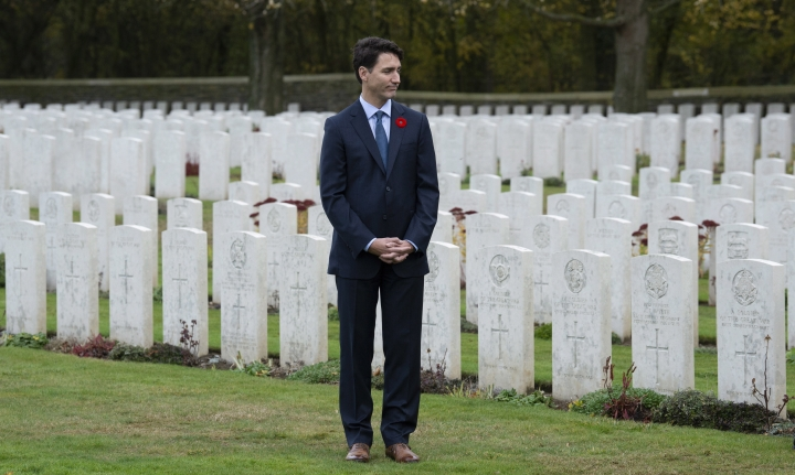 Canadian Prime Minister Justin Trudeau stands among the military gravestones as he visits the Canadian Cemetery No. 2 near Vimy Ridge, France, Saturday Non. 10, 2018. (Adrian Wyld/The Canadian Press via AP)