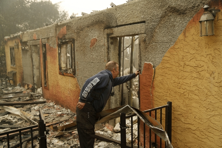 Courtenay Jenvey inspects the remains of his neighbor's home Saturday, Nov. 10, 2018, in Paradise, Calif. Jenvey was able to save his house during the fire. (AP Photo/John Locher)