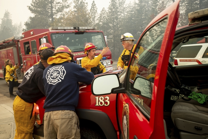 Firefighters plan their operations while battling the Camp Fire in Paradise, Calif., on Saturday, Nov. 10, 2018. The blaze that started Thursday outside the hilly town of Paradise has grown and destroyed more than 6,700 buildings, almost all of them homes, making it California's most destructive wildfire since record-keeping began. But crews have made gains and the fire is partially contained, officials said Saturday. (AP Photo/Noah Berger)