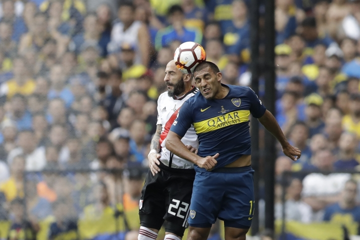Ramón Abila of Argentina's Boca Juniors, right, and Javier Pinola of Argentina's River Plate go for a header during a Copa Libertadores first leg final match in Buenos AIres, Argentina, Sunday, Nov. 11, 2018. (AP Photo/Natacha Pisarenko)