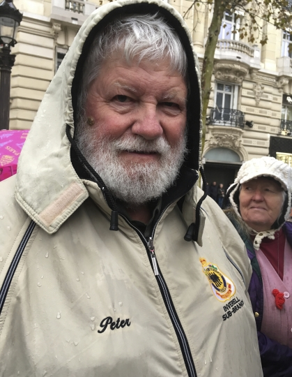 Peter Kearsey poses for a photo in Paris, Sunday Nov. 11, 2018. Kearsay is the son of Australian soldier William Kearsay whose face was badly damaged in World War I while fighting in Belgium with Australia's 33rd Battalion. He survived _ after 28 surgeries to reconstruct his face. Peter Kearsey, was among hundreds lining the rain-soaked Champs-Elysees Avenue in Paris on Sunday to honor along with world leaders those who fought in the Great War 100 years after it ended. (AP Photo/Elaine Ganley)