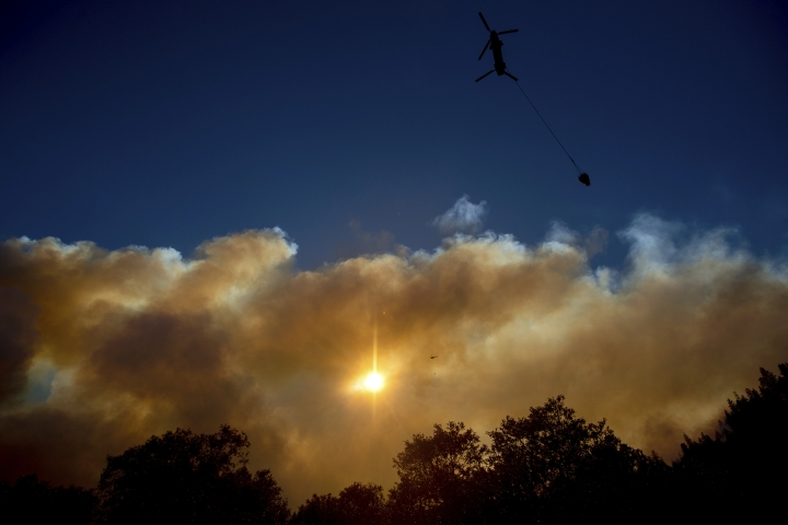 Smoke billows from the Camp Fire as a firefighting helicopter flies near Pulga, Calif., on Sunday, Nov. 11, 2018. (AP Photo/Noah Berger)