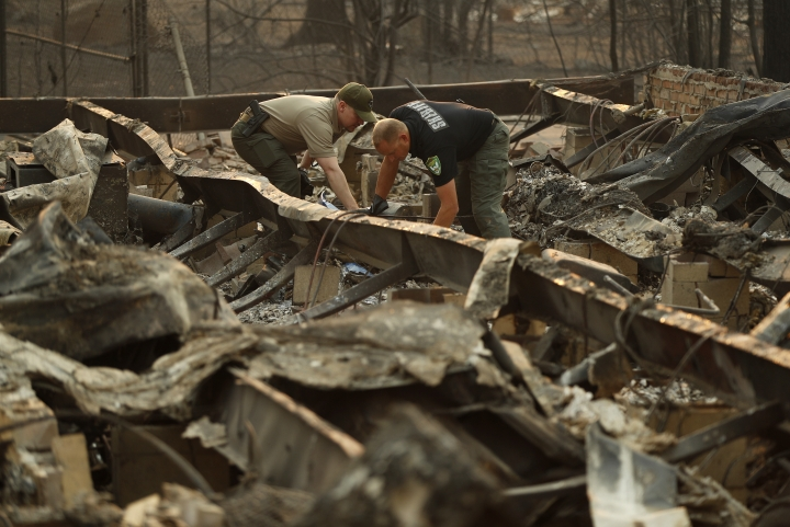 Sgt. Nathan Lyberger, of the Yuba County Sheriff's Department, right, and Sgt. Kevin Packard, of the Mariposa County Sheriff's Office, prepare to move human remains found at a burned out home from the Camp Fire, Sunday, Nov. 11, 2018, in Paradise, Calif. (AP Photo/John Locher)