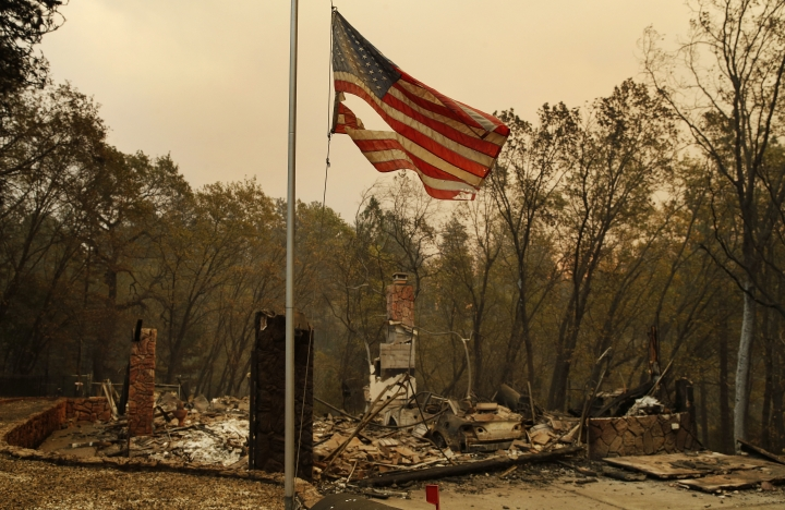 A tattered flag flies over a burned out home at the Camp Fire, Sunday, Nov. 11, 2018, in Paradise, Calif. (AP Photo/John Locher)