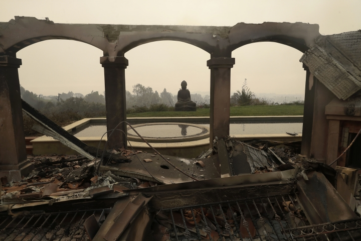 A Buddha statue stands among the damage caused by a wildfire at a home Saturday, Nov. 10, 2018, in Malibu, Calif. Scores of houses from ranch homes to celebrities' mansions burned in a pair of wildfires that stretched across more than 100 square miles of Southern California, authorities said Saturday. (AP Photo/Marcio Jose Sanchez)