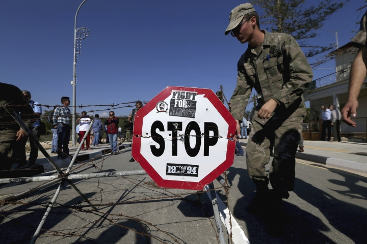 A Cypriot soldier removes the barbed-wire that blocked the road, at a newly-opened crossing point between ethnically split Cyprus' internationally recognized south and the breakaway, Turkish Cypriot north at the southeastern village of Dherynia on Monday, Nov. 12, 2018. A few hundred Greek Cypriots and Turkish Cypriots walked through a newly opened crossing point in the southeastern village of Dherynia in what peace activists are hailing as further breaking down barriers on ethnically divided Cyprus. (AP Photo/Petros Karadjias)