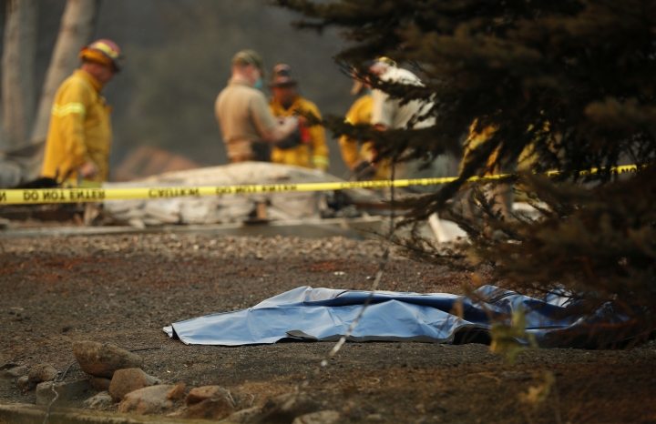 A bag containing human remains lies on the ground as officials continue to search at a burned out home at the Camp Fire, Sunday, Nov. 11, 2018, in Paradise, Calif. (AP Photo/John Locher)
