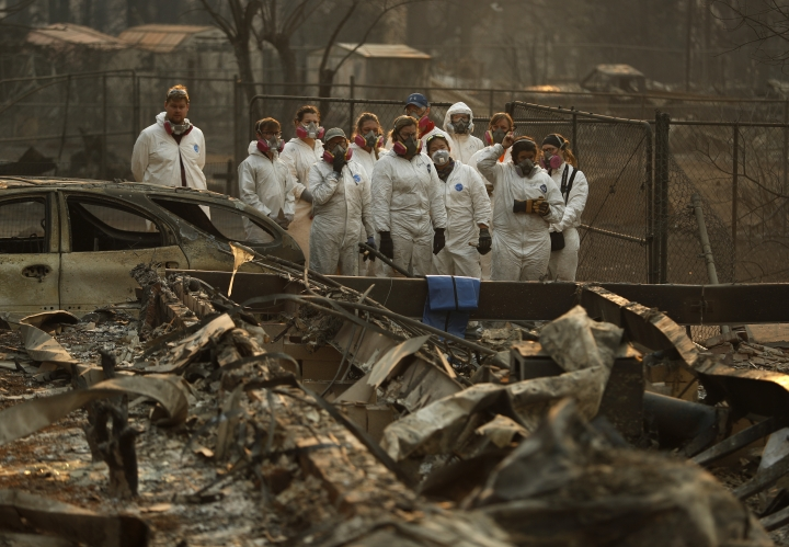 Anthropology students observe as human remains are recovered from a burned out home at the Camp Fire, Sunday, Nov. 11, 2018, in Paradise, Calif. (AP Photo/John Locher)