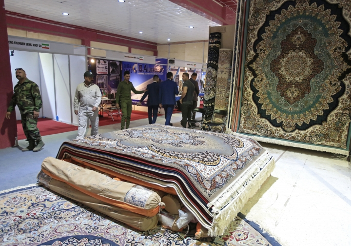 In this Saturday, Nov. 10, 2018 photo, visitors tour the Iranian wing of the Baghdad International Fair, in Baghdad, Iraq. Iran, already feeling the bite of U.S. sanctions, is turning to its neighbor Iraq to soak up some of its exports in agriculture, manufacturing and energy. At the Baghdad International Fair, Iran's ambassador says he wants to triple trade with Iraq. (AP Photo/Karim Kadim)