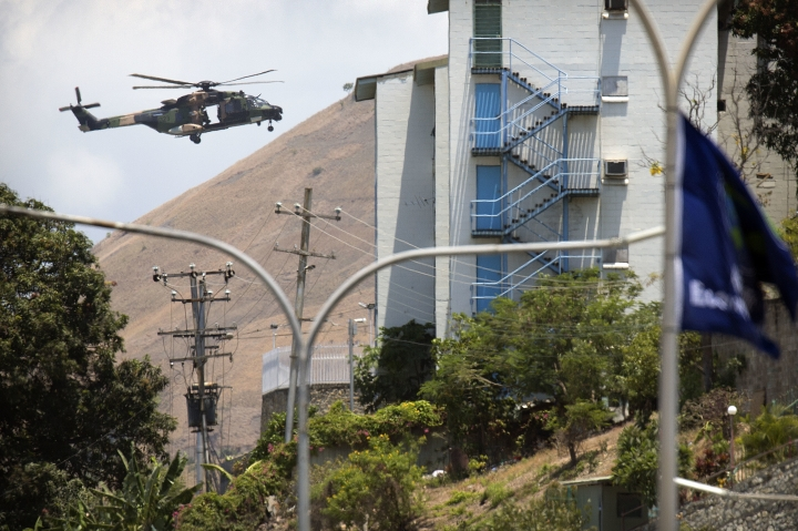 A military helicopter flies over a neighborhood ahead of the APEC Economic Leaders' Week Summit in Port Moresby, Papua New Guinea, Wednesday, Nov. 14, 2018. After three decades of promoting free trade as a panacea to poverty, the APEC grouping of nations that includes the U.S. and China is holding its lavish annual leaders meeting in the country that can least afford it. (AP Photo/Mark Schiefelbein)