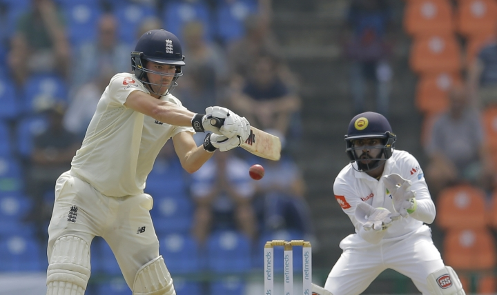 England's Rory Burns , left, plays a shot as Sri Lanka's Niroshan Dickwella watches during the first day of the second test cricket match between Sri Lanka and England in Pallekele, Sri Lanka, Wednesday, Nov. 14, 2018. (AP Photo/Eranga Jayawardena)