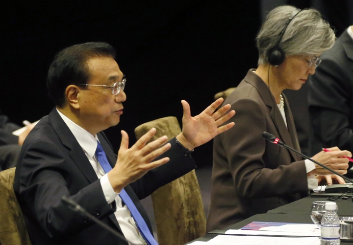Chinese Premier Li Keqiang, left, delivers his statement at the ASEAN Plus Three Summit in the ongoing 33rd ASEAN Summit and Related Summits Thursday, Nov. 15, 2018, in Singapore. At right is South Korean Foreign Minister Kang Kyung-wha, who represented South Korean President Moon Jae-in. (AP Photo/Bullit Marquez)