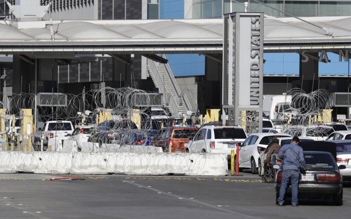 Barricades with concertina wire block three lanes at the San Ysidro port of entry Wednesday, Nov. 14, 2018, as seen from Tijuana, Mexico. Migrants in a caravan of Central Americans scrambled to reach the U.S. border, catching rides on buses and trucks for hundreds of miles in the last leg of their journey Wednesday as the first sizable groups began arriving in the border city of Tijuana. (AP Photo/Gregory Bull)