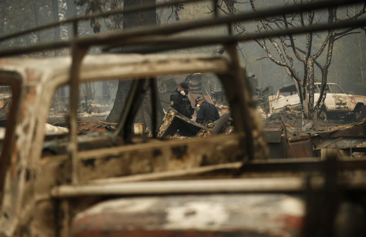 Sheriff deputies look at a spot that may contain human remains at a home burned in the Camp Fire, Thursday, Nov. 15, 2018, in Magalia, Calif. (AP Photo/John Locher)