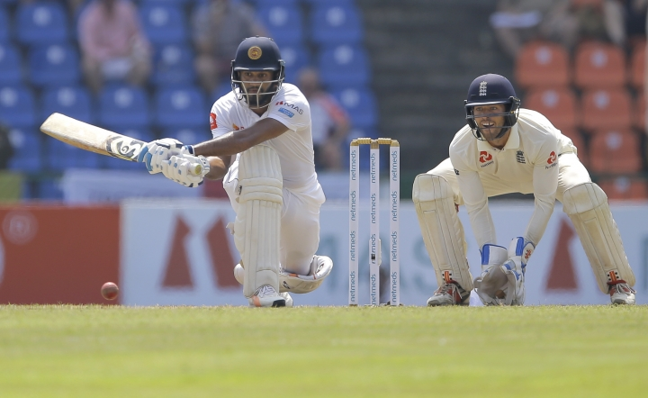 Sri Lankan Dhananjaya de Silva plays a shot as England's wicketkeeper Ben Foakes watches during the second day of the second test cricket match between Sri Lanka and England in Pallekele, Sri Lanka, Thursday, Nov. 15, 2018. (AP Photo/Eranga Jayawardena)