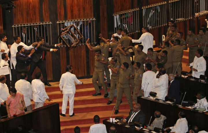 Lawmakers supporting disputed Prime Minister Rajapksa throw a chair towards police officers escorting the speaker inside parliament in Colombo, Sri Lanka, Friday, Nov. 16, 2018. Pandemonium reigned in Sri Lanka's Parliament as lawmakers supporting Rajapaksa violently demonstrated in the house to prevent the proceedings from taking place on Friday, a day after a fierce brawl between rival legislators. They threw books and chairs at police who escorted Jayasuriya into the chamber and did not allow him to sit in the speaker's chair. Jayasuriya, using a microphone, adjourned the house until Monday. (AP Photo/Lahiru Harshana)