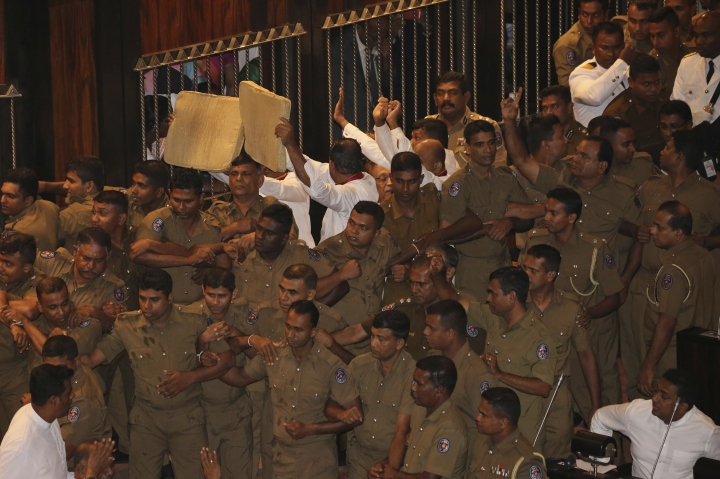 Lawmakers supporting ousted prime minister Ranil Wickremesinghe and policemen form a cordon around Speaker Karu Jayasuriya, in black robe, inside parliament in Colombo, Sri Lanka, Friday, Nov. 16, 2018. Pandemonium reigned in Sri Lanka's Parliament as lawmakers supporting disputed Prime Minister Mahinda Rajapaksa violently demonstrated in the house to prevent the proceedings from taking place on Friday, a day after a fierce brawl between rival legislators. They threw books and chairs at police who escorted Jayasuriya into the chamber and did not allow him to sit in the speaker's chair. Jayasuriya, using a microphone, adjourned the house until Monday. (AP Photo/Lahiru Harshana)