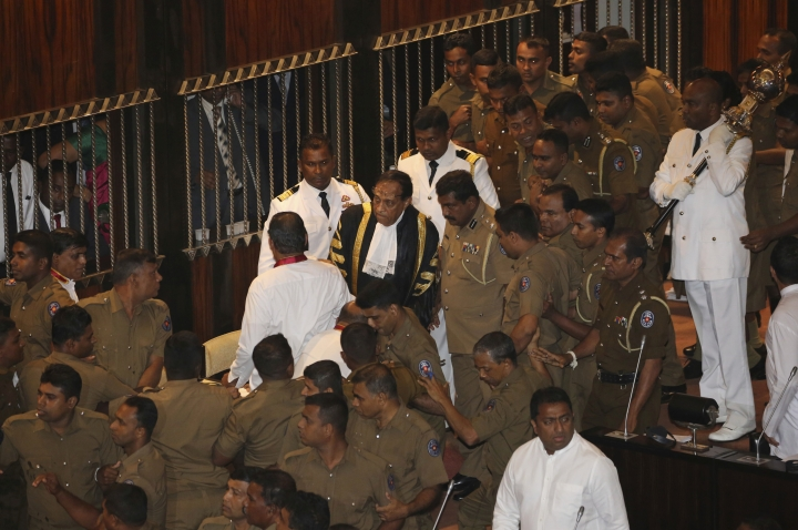 Policemen escort Speaker Karu Jayasuriya, in black robe, inside parliament in Colombo, Sri Lanka, Friday, Nov. 16, 2018. Pandemonium reigned in Sri Lanka's Parliament as lawmakers supporting disputed Prime Minister Mahinda Rajapaksa violently demonstrated in the house to prevent the proceedings from taking place on Friday, a day after a fierce brawl between rival legislators. They threw books and chairs at police who escorted Jayasuriya into the chamber and did not allow him to sit in the speaker's chair. Jayasuriya, using a microphone, adjourned the house until Monday. (AP Photo/Lahiru Harshana)
