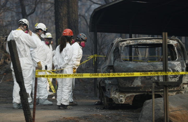 Search and rescue personnel peer into a car with suspected human remains at the Camp Fire, Friday, Nov. 16, 2018, in Paradise, Calif. (AP Photo/John Locher)