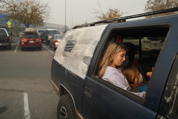 Dakota Keltner, right, rests on Havyn Cargill-Morris in a truck at a makeshift encampment outside a Walmart store for people displaced by the Camp Fire, Friday, Nov. 16, 2018, in Chico, Calif. The two, from Magalia, Calif., escaped the fire with their families. (AP Photo/John Locher)