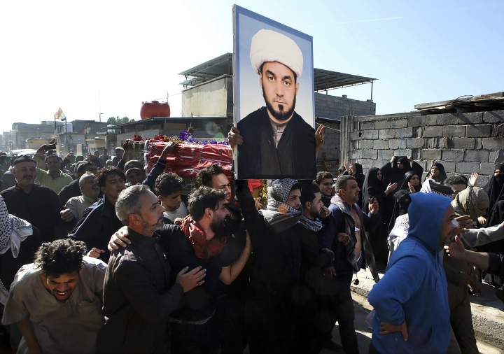 Mourners chant anti-government slogans while they carry the coffin of prominent social activist Wissam al-Ghrawi in Basra, Iraq, Sunday, Nov. 18, 2018. Iraqi police say religious cleric Wissam, who was linked to the ongoing protests over poor services in Basra, was killed outside his home after suggested that demonstrators should take up arms over the conditions in the city. (AP Photo/Nabil al-Jurani)