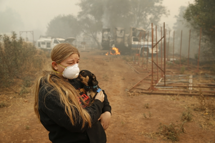 In this Nov. 10, 2018, photo, Arianne Harvey holds her dog T.J. near a truck still on fire from the Camp Fire in Paradise, Calif. Harvey was living in an RV near where her family's home was destroyed by the fire. For a while, Phillip and Krystin Harvey, who lost their mobile home, had been staying with Arianne and their two other teenage daughters in the camper, trying to hang on to a piece of the life they had known. Eventually the family gave up and moved to Oroville, Calif., to stay with friends to have some stability and security, their cousins Patrick Knuthson said. (AP Photo/John Locher)