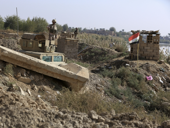 In this Tuesday, Nov. 13 2018 photo, Iraqi soldiers stand on the Iraqi side of the border with Syria, in the town of Qaim, Anbar province, Iraq. Life in Qaim has been put on hold as just across the border in Syria, fighting rages against one of the last major enclaves of the Islamic State group. (AP Photo/Hadi Mizban)