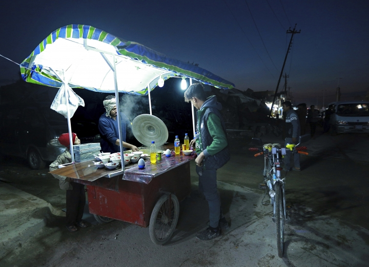 In this Monday, Nov. 12, 2018 photo, a street vendor sells chickpeas, in Qaim, Anbar province, Iraq. Life in Qaim has been put on hold as just across the border in Syria, fighting rages against one of the last major enclaves of the Islamic State group. The town was once a thriving stopover on the highway between Damascus and Baghdad. (AP Photo/Hadi Mizban)