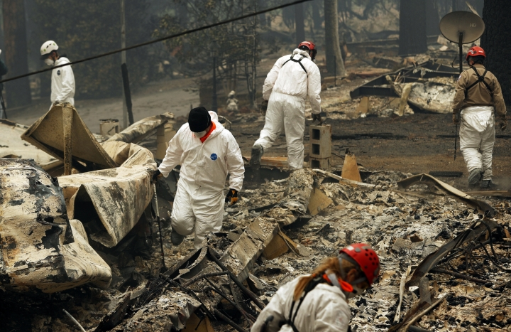 FILE - In this Tuesday, Nov. 13, 2018 file photo, search and rescue workers search for human remains at a trailer park burned out from the Camp fire in Paradise, Calif. Officials say the search to find the missing and identify victims could take months given the size and scope of the deadly wildfire that swept Northern California's Gold Rush country. The Camp Fire in Butte County that started two weeks ago has killed multiple people and hundreds of names are on a fluctuating list of the unaccounted. (AP Photo/John Locher, File)