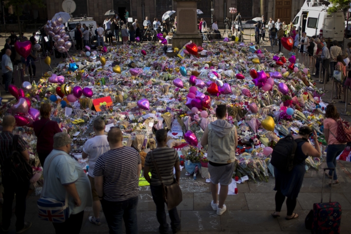 FILE - In this Friday, May 26, 2017 file photo, people stand next to tributes placed in St Ann's Square in central Manchester, England, after Monday's bombing. A major British parliamentary report found Thursday Nov. 22, 2018, that shortcomings by security services led to missed opportunities to possibly prevent last year's lethal extremist attack at Manchester Arena. (AP Photo/Emilio Morenatti, File)