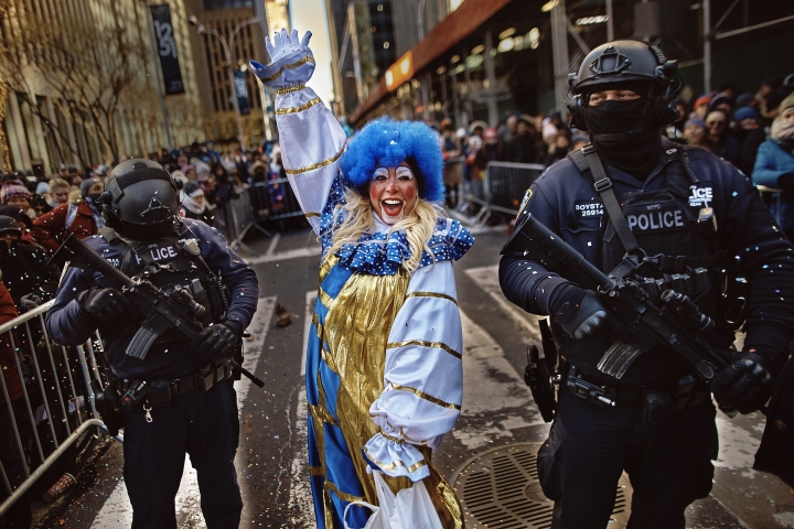 A clown performs as heavily armed police stand guard along Sixth Avenue during the Macy's Thanksgiving Day Parade in New York, Thursday, Nov. 22, 2018. (AP Photo/Andres Kudacki)