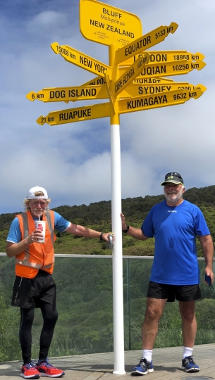 In this Wednesday, Nov. 21, 2018 photo, Perry Newburn, left, stands with support crew member Graeme Calder at Stirling Point in Bluff at the bottom of the South Island of New Zealand. Powered by chocolate milkshakes and hash browns, 64-year-old Newburn has completed running the length of New Zealand in a record time of 18 days and eight hours. (Kashif Shuja via AP)