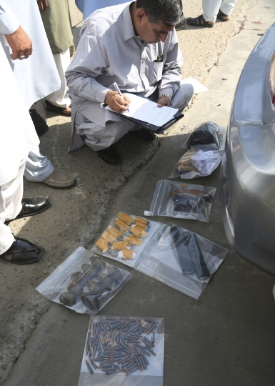 A police officer checks ammunition recovered during an attack at the Chinese Consulate in Karachi, Pakistan, Friday, Nov. 23, 2018. Armed separatists stormed the Chinese Consulate in Pakistan's southern port city of Karachi on Friday, triggering an intense hour-long shootout during which two police officers and all three assailants were killed, Pakistani officials said. (AP Photo/Shakil Adil)