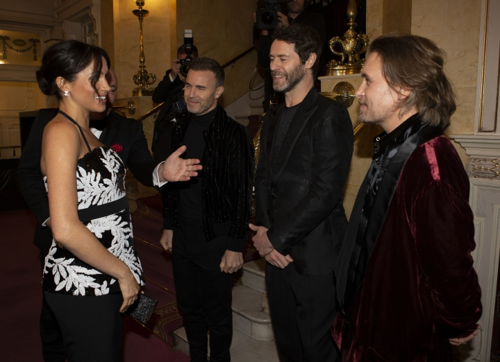 "Meghan, the Duchess of Sussex talks to from left Gary Barlow, Howard Donald and Mark Owen of the group ""Take That"" as she arrives with Britain's Prince Harry to attend the Royal Variety Performance at the London Palladium in central London, Monday, Nov. 19, 2018. (Ian Vogler/Pool Photo via AP)"