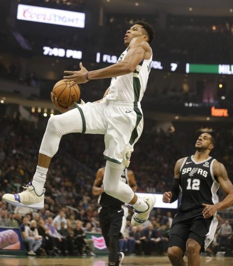 Milwaukee Bucks' Giannis Antetokounmpo, left, winds up for a dunk against San Antonio Spurs' LaMarcus Aldridge (12) during the first half of an NBA basketball game Saturday, Nov. 24, 2018, in Milwaukee. (AP Photo/Jeffrey Phelps)