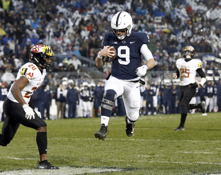 Penn State quarterback Trace McSorley (9) runs in for a touchdown in front of Maryland's Antwaine Richardson (20) during the first half of an NCAA college football game in State College, Pa., Saturday, Nov. 24, 2018. (AP Photo/Chris Knight)