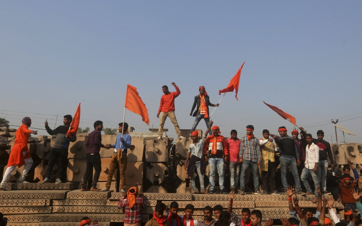 Supporters of Vishwa Hindu Parishad or World Hindu Council stand on blocks prepared for making a new temple as they gather for a rally to demand the construction of a Ram temple in Ayodhya, India, Sunday, Nov.25, 2018. Tens of thousands of Hindus gathered in the northern Indian city renewing calls to build a Hindu temple on a site where a mosque was attacked and demolished in 1992, sparking deadly Hindu-Muslim violence. (AP Photo)
