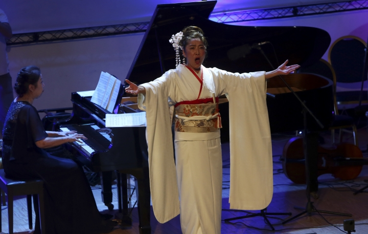 Japanese pianist Kaoru Imahigashi plays the piano while opera singer Fujiko Hirai, right, perform during a concert to mark the debut of Gaza's only grand piano after it was rescued from conflict, at a theater nestled in the Palestinian Red Crescent Society's building in Gaza City, Sunday, Nov. 25, 2018. The only grand piano in the Gaza Strip is debuting to the public for the first time in over a decade after its restoration. (AP Photo/Adel Hana)