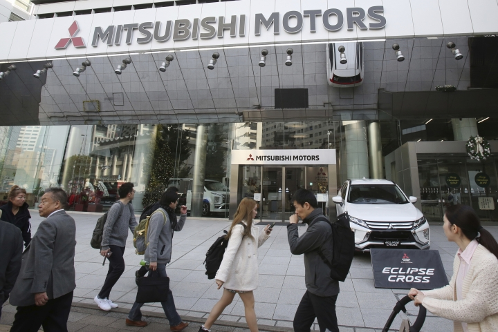 People walk past the headquarters of Mitsubishi Motors Corp in Tokyo, Monday, Nov. 26, 2018. The board of Mitsubishi Motors is meeting Monday to decide whether to oust Carlos Ghosn as chairman at the Japanese automaker, which is allied with Renault-Nissan. (AP Photo/Koji Sasahara)