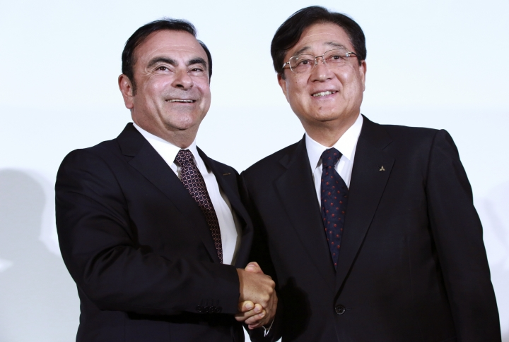FILE - In this May 12, 2016, file photo, then Nissan Motor Co. President and CEO Carlos Ghosn, left, and Mitsubishi Motors Corp. Chairman and CEO Osamu Masuko pose for photographers after their joint press conference at the Nissan headquarters in Yokohama, near Tokyo. The board of Mitsubishi Motors is meeting Monday, Nov. 26, 2018, to decide whether to oust Carlos Ghosn as chairman at the Japanese automaker, which is allied with Renault-Nissan. (AP Photo/Eugene Hoshiko, File)