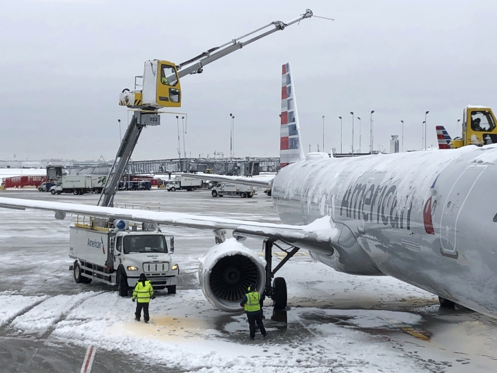 Crews de-ice an American Airlines plane at O'Hare International Airport on Monday, Nov. 26, 2018, in Chicago. A wintry storm brought blizzard-like conditions to parts of the Midwest early Monday, grounding hundreds of flights and causing slick roads for commuters as they returned to work after the Thanksgiving weekend. (AP Photo/Noreen Nasir)