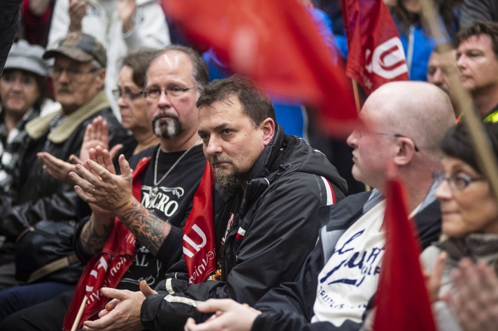 Workers of Oshawa's General Motors car assembly plant, listen to Jerry Dias, president of UNIFOR, the union representing the workers, at the union headquarters in Oshawa, Ont. on Monday, Nov. 26, 2018. (Eduardo Lima/The Canadian Press via AP)