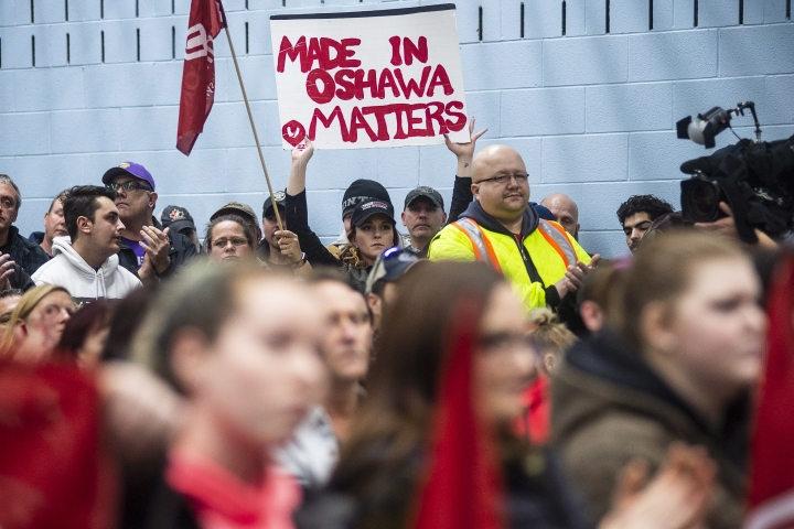 Workers of Oshawa's General Motors car assembly plant, listen to Jerry Dias, president of UNIFOR, the union representing the workers, at the union headquarters, in Oshawa, Ont. on Monday, Nov. 26, 2018. (Eduardo Lima/The Canadian Press via AP)