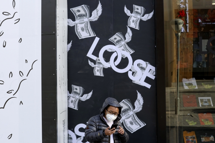"A man stands near a billboard depicting bundles of flying U.S. dollars at a retail district in Beijing, China, Tuesday, Nov. 27, 2018. Asian markets clocked more gains Tuesday ahead of a meeting between the U.S. and China at the Group of 20 summit this week, despite President Donald Trump's comments that it's ""highly unlikely"" he'll hold off on raising tariffs as Beijing requested. (AP Photo/Ng Han Guan)"