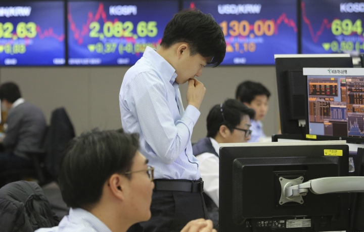 """A currency trader watches monitors at the foreign exchange dealing room of the KEB Hana Bank headquarters in Seoul, South Korea, Tuesday, Nov. 27, 2018. Asian markets clocked more gains Tuesday ahead of a meeting between the U.S. and China at the Group of 20 summit this week, despite President Donald Trump's comments that it's """"highly unlikely"""" he'll hold off on raising tariffs as Beijing requested. (AP Photo/Ahn Young-joon)"""