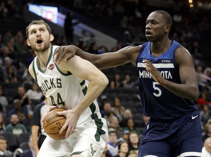 FILE - In this Oct. 12, 2018, file photo, Milwaukee Bucks center Tyler Zeller, left, looks to shoot as Minnesota Timberwolves center Gorgui Dieng defends during an NBA preseason basketball game in Milwaukee. When USA Basketball resumes its quest to qualify for the 2019 FIBA World Cup, Zeller will be wearing the red, white and blue in an international game for the first time. The NBA veteran and current free agent is one of the 12 players on the squad for this two-game window of qualifying, which starts with a crucial matchup Thursday at Argentina. (AP Photo/Mike Roemer, File)