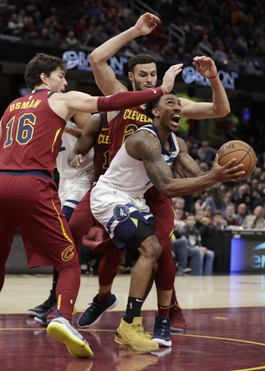 Minnesota Timberwolves' Jeff Teague, center, drives to the basket between Cleveland Cavaliers' Cedi Osman, left, from Turkey, and Larry Nance Jr. in the second half of an NBA basketball game, Monday, Nov. 26, 2018, in Cleveland. (AP Photo/Tony Dejak)